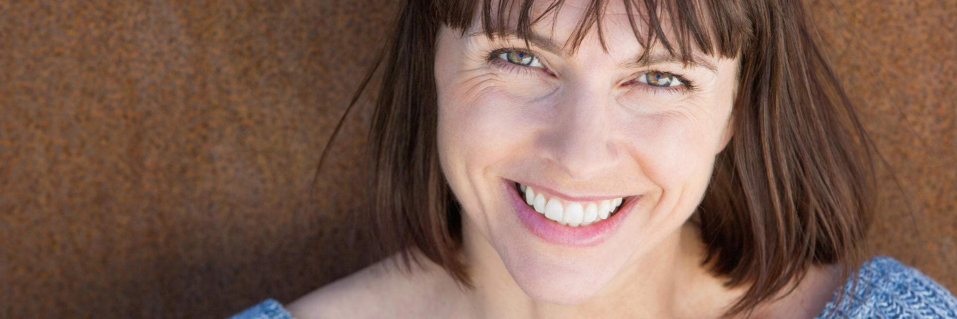Happy brunette middle-aged woman showing nice teeth in her smile.