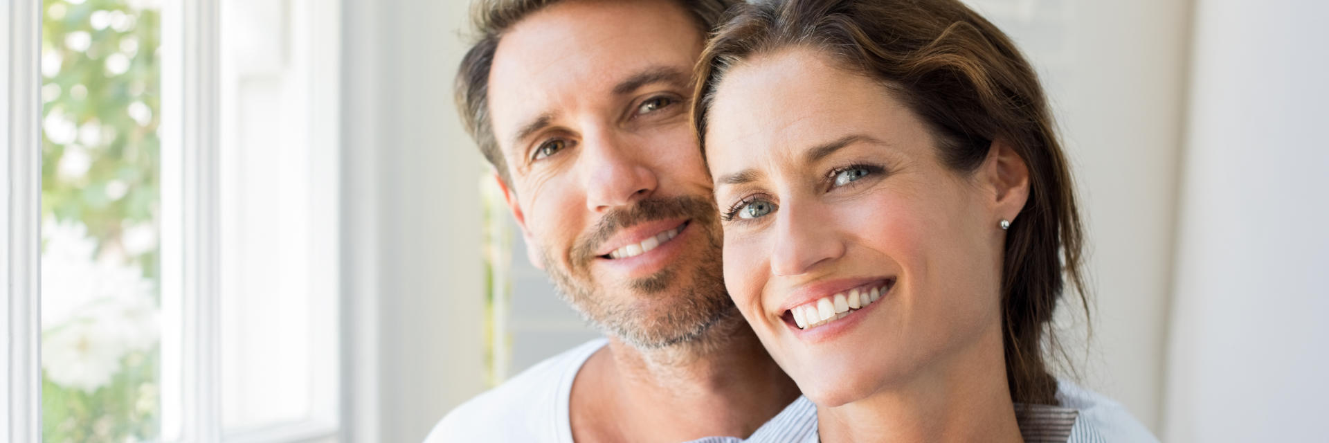 Happy middle-aged couple showing their nice teeth after dental crowns treatment in their smiles.