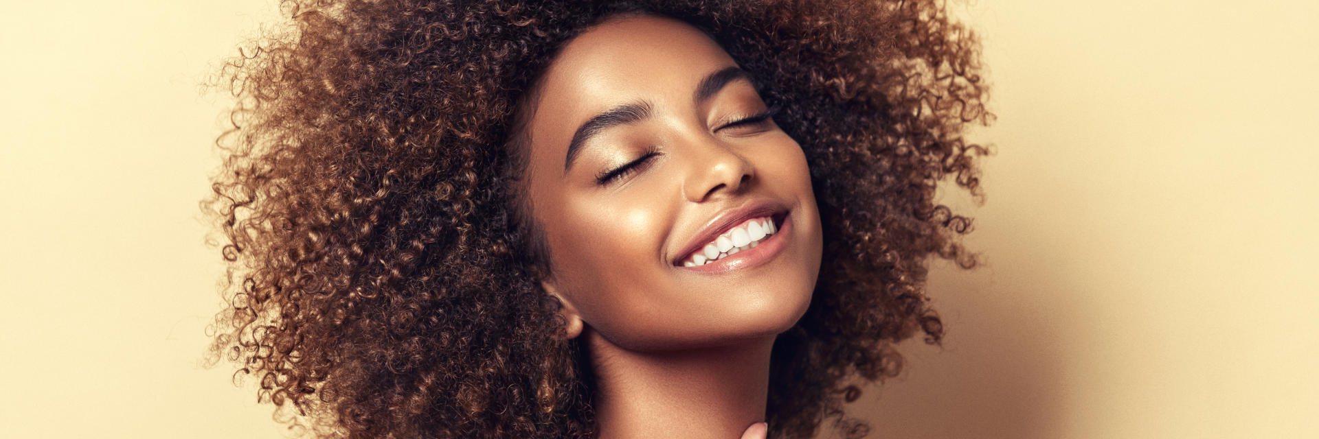 Happy young Afro-American woman showing her beautiful teeth in smile.