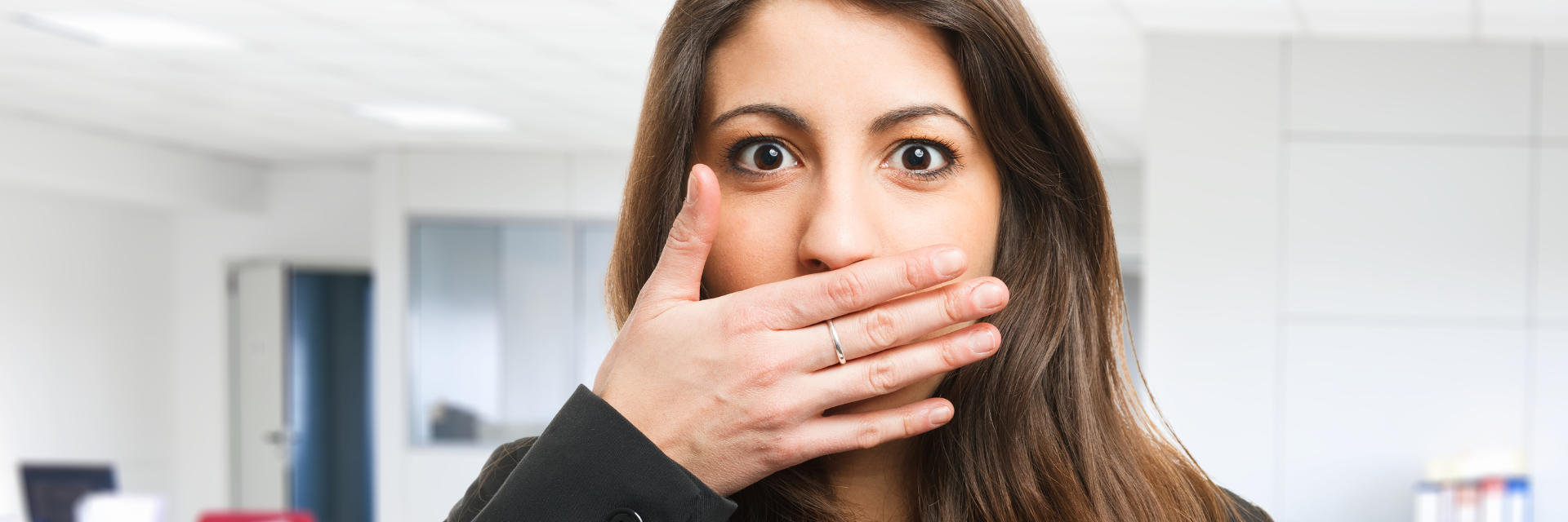 Concerned young woman covering her mouth due to bad breath.