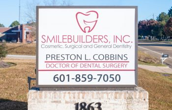 SmileBuilders, Inc. informative sign in front of the dentistry building.