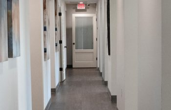 A corridor with paintings on the walls at SmileBuilders, Inc. Cosmetic, Surgical and General Dentistry.