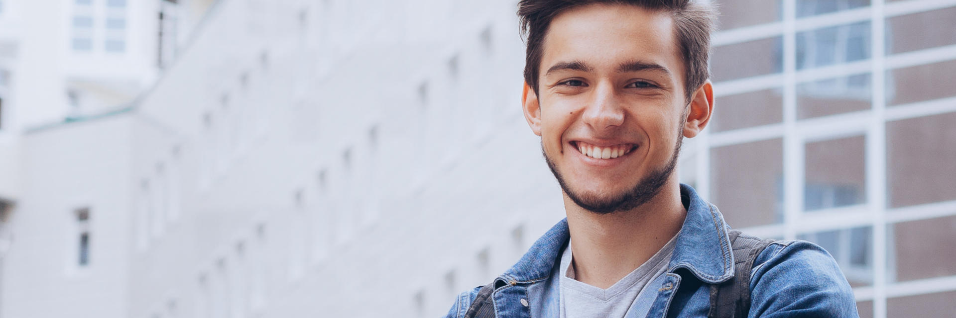 Happy young man with perfect smile in front of office buildings.