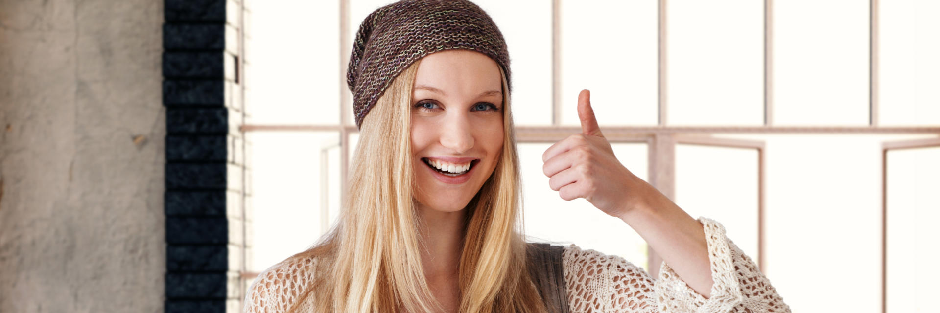 Young blonde woman with perfect smile showing her thumb up.