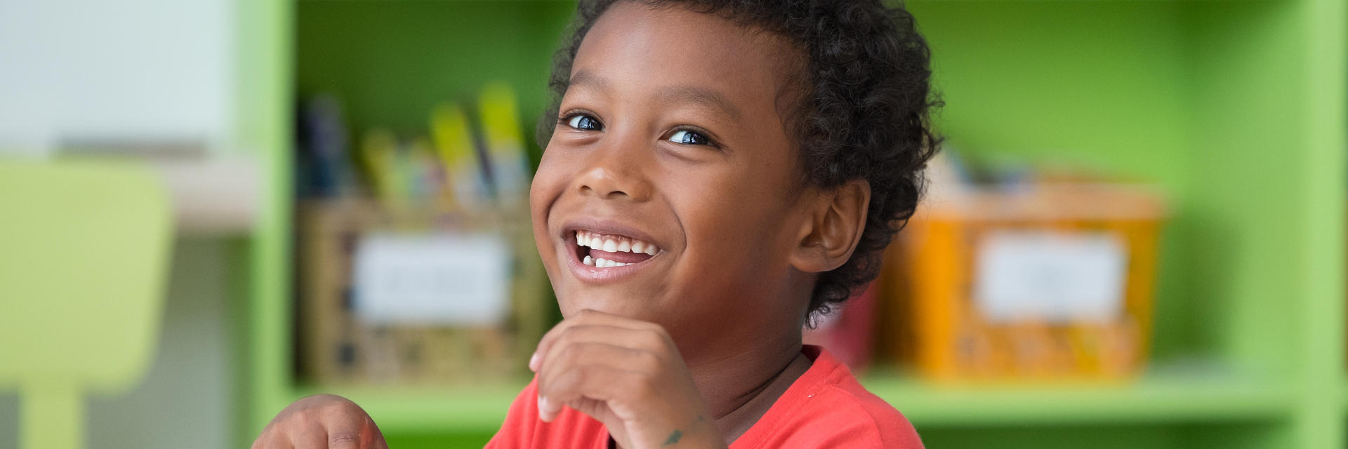 Happy Afro-American little boy showing his teeth in a smile.