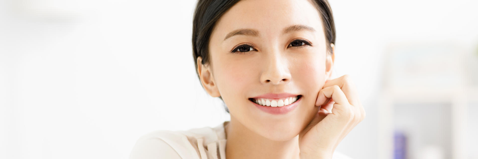 Cheerful young Asian woman showing nice whitened teeth in her teeth.