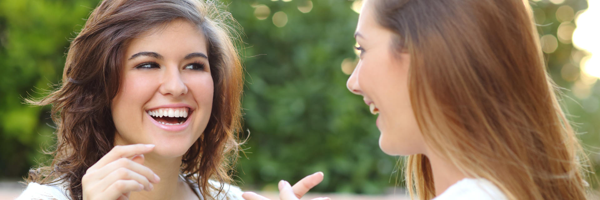 Two cheerful young women with perfect smiles chatting in the park.