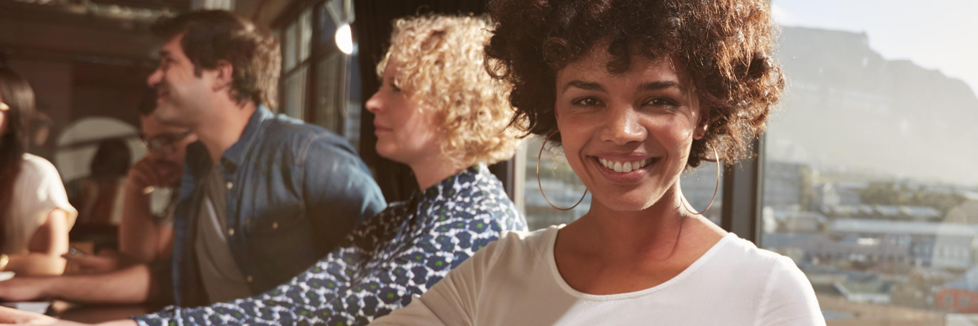 Cheerful Afro-American woman with a perfect smile socializing with friends.
