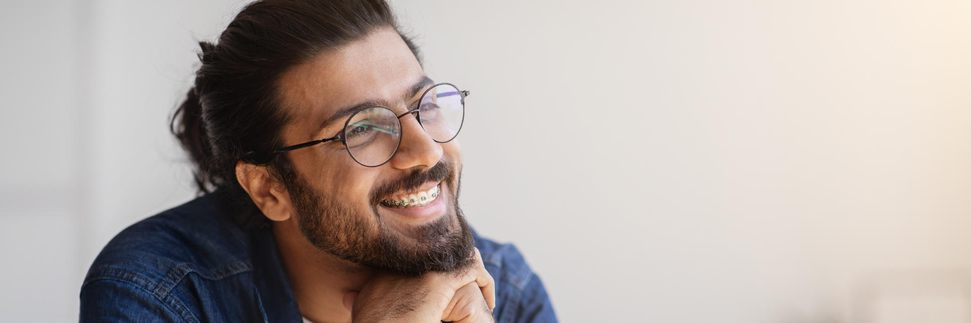 Smiling adult man wearing orthodontic braces.